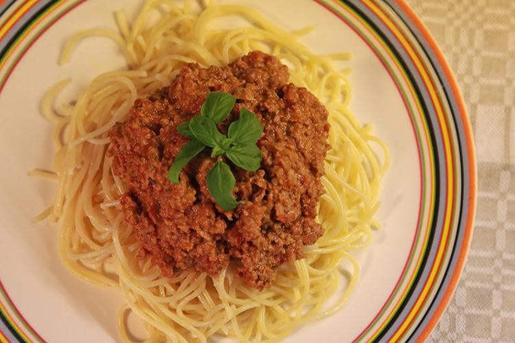 Spagetti med färssås ovanpå, dekorerat med basilika