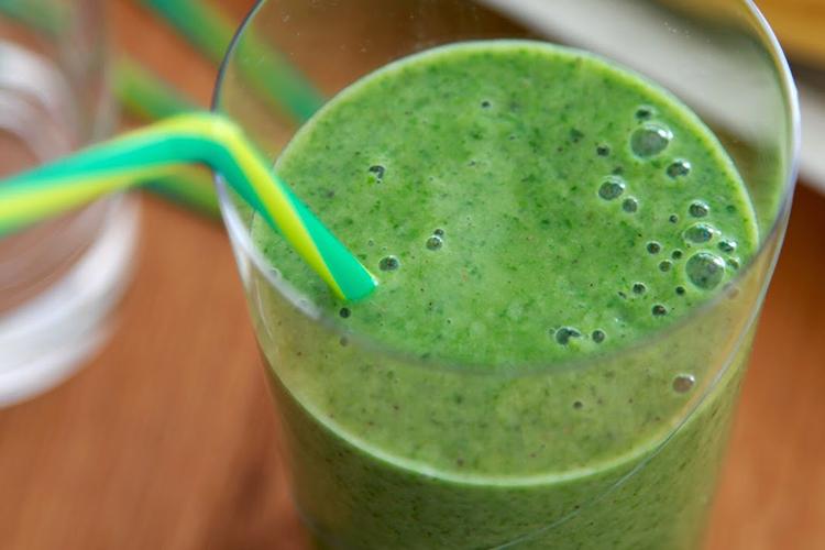 Grön smoothie i högt glas med sugrör