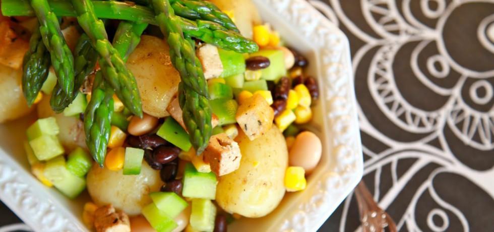 Sallad med potatis, gurka, bönor, tofu och majs toppad med sparris på vitt fat. Står på en duk med svart och vitt mönster