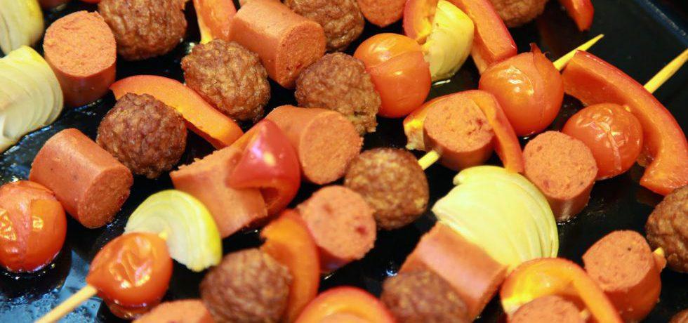 Spettpinnar med vegobullar, körsbärstomater, korv, paprika och gul lök på