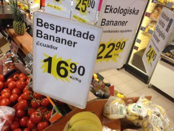 """Bild på butiksskyltning av bananer, en skylt anger """"Besprutade Bananer"""" den andra """"Ekologiska Bananer"""" samt prisuppgift."""