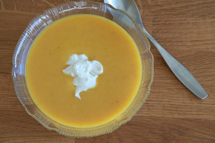 Gul morotssoppa i glasskål med sked till höger sett uppifrån