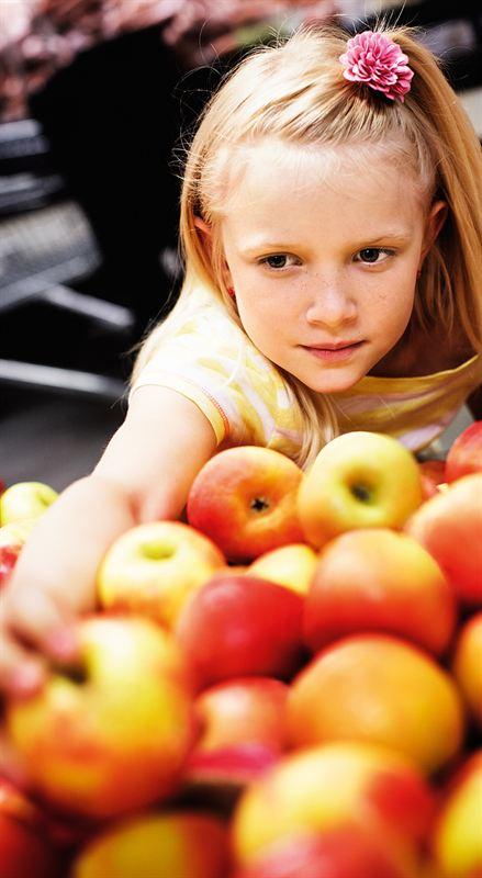 En flicka vid en fruktdisk full med rödgula äpplen sträcker ut handen för att ta ett äpple