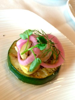 En grillad, rund zucchinibit på vitt fat med böncrème och picklad rödlök ovanpå