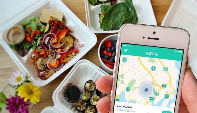 Smartphone med appen ResQclub uppe, i bakgrunden vita fat med bär och grönsaker.