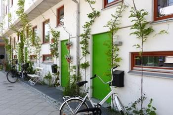 Husbyggnad, vit fasad med gröna dörrar, klängväxter växer upp längs väggen vid sidorna av de båda dörrarna, vit cykel parkerad framför den ena i förgrunden.