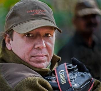 Porträttbilld på Tom Svensson, vit medelåldersman i militärgrön keps, kamera syns nedtill
