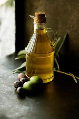 En glaskanna med olja på ett träbord