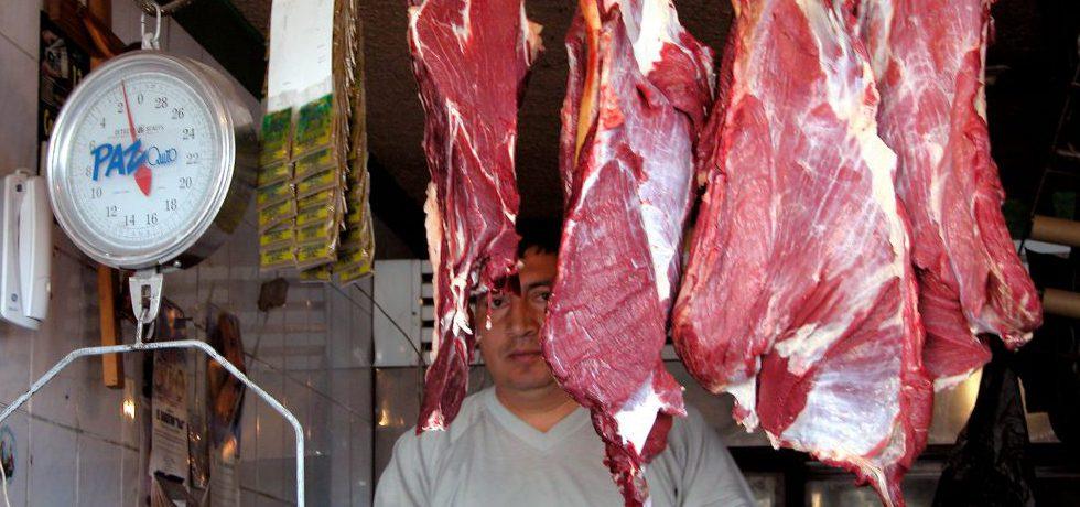 En man står bakom styckade, upphängda köttdelar