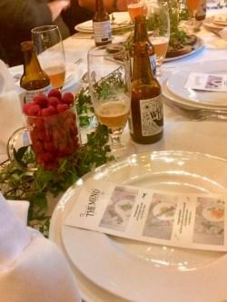 Brun ölflaska till höger om ölglas med lite öl intill tallrik och bestick på vit linneduk. Bredvid stort ölglas fyllt med färska hallon, diukningen dekorerad med gröna blad