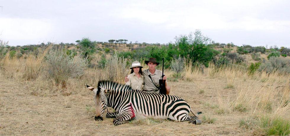 En kvinna och en man poserar bakom en ihjälskjuten zebra. Mannen håller ett gevär i vänster hand.