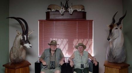 En man och en kvinna sitter i varsin fåtölj omgivna av uppstoppade djur.