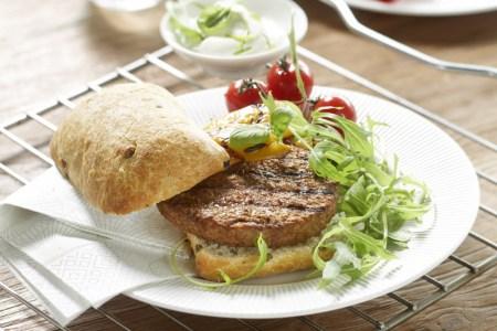 Tallrik med vegetarisk burgare med ciabattabröd med sallad och cocktailtomater, i bakgrunden ett vitt fat med yoghurtsås