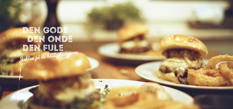 Ett bord där det står tre tallrikar med hamburgare med bröd på samt pommes. En kryddkvarn står i bakgrunden