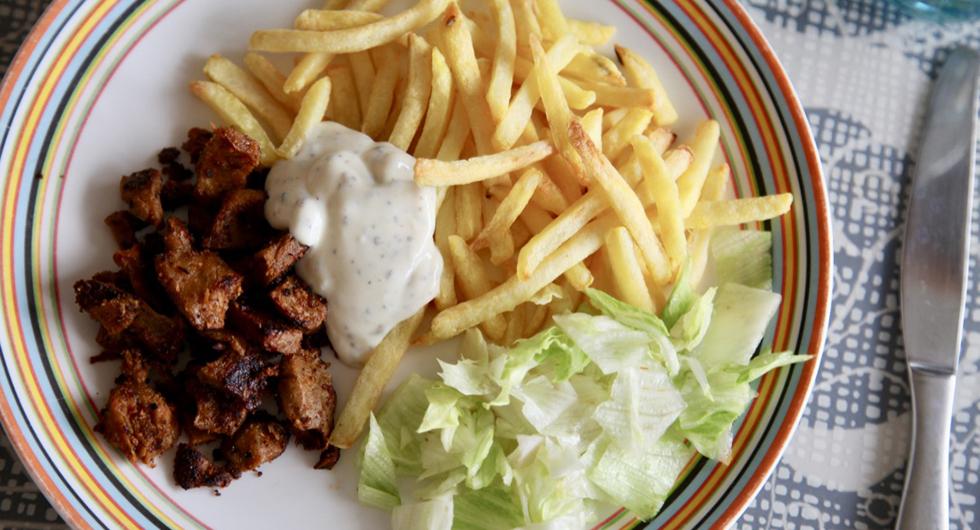 En tallrik sedd uppifrån med kebab, pommes, isbergssallat och i mitten en vit sås