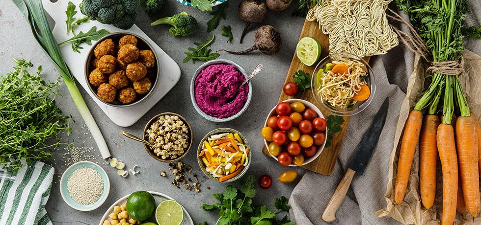 Grönsaker i skålar och på skärbrädor sedda uppifrån, majsbollar i en skål till vänster
