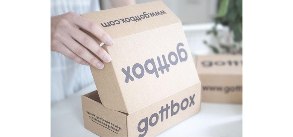 En kartong med texten gottbox på, som öppnas, hand syns till vänster
