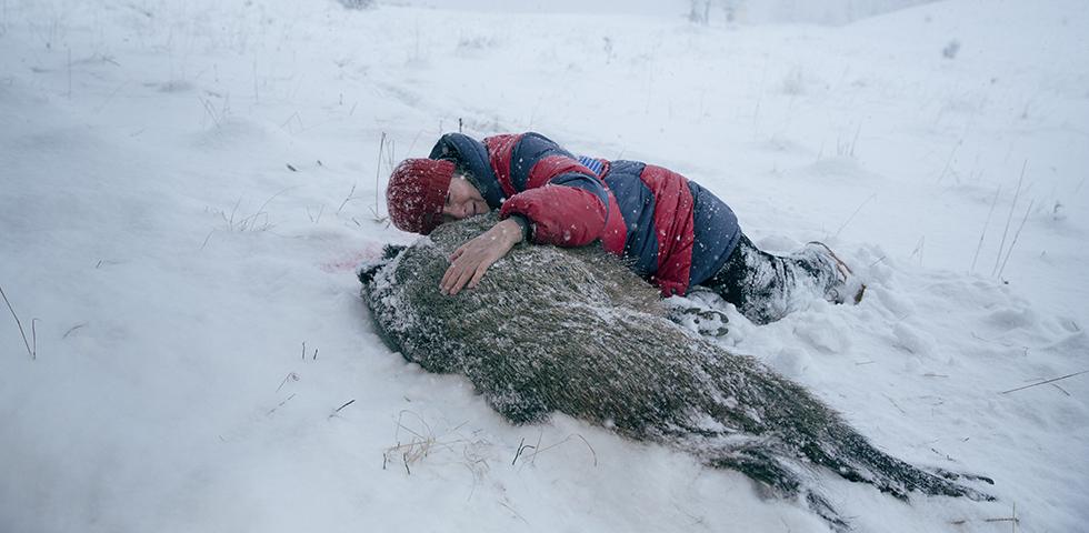 Kvina med röd mössa och röd/blårandig täckjacka ligger i snön och håller om ett dött djur