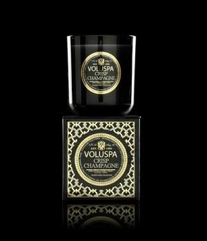 Svart värmeljus i glas ovanpå en guld- och svartfärgad förpackning