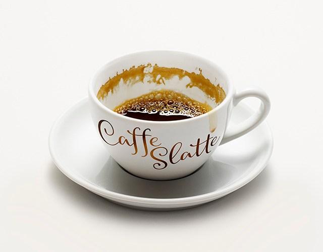 Vit kaffekopp på fat med texten Caffe Slatte i brunt på