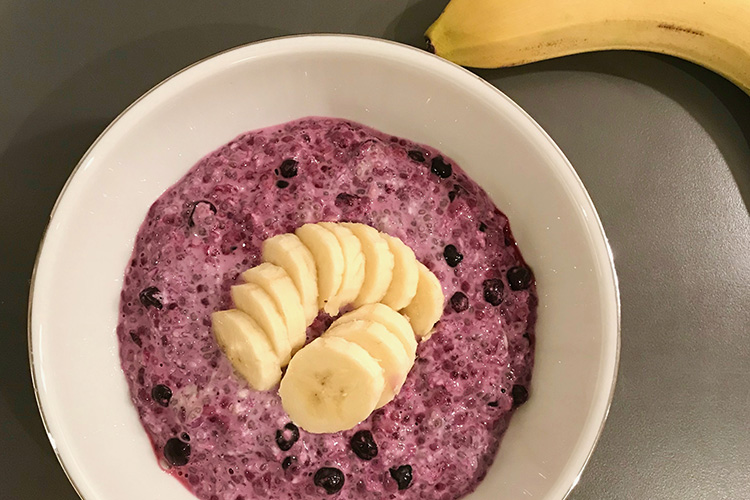 En skål med lilafärgad gröt, skivad banan ovanpå, en banan vanför skålen