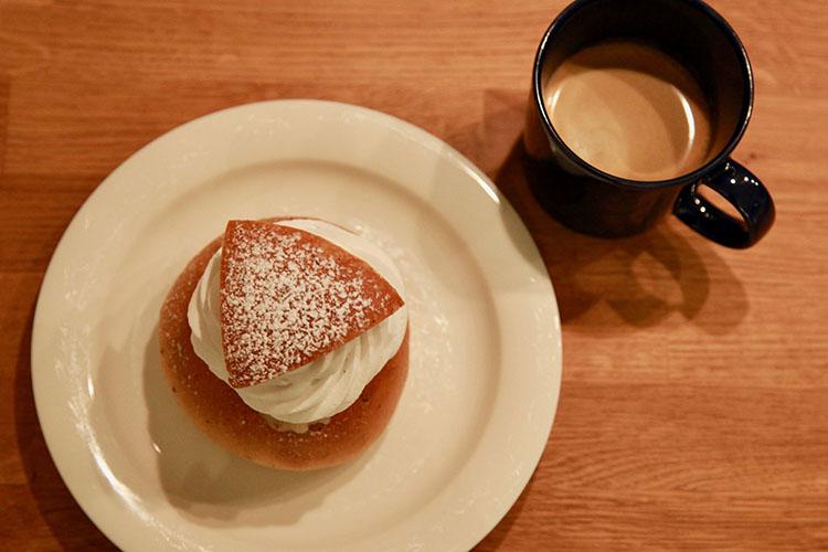 Semla på vitt fat, bredvid en kopp kaffe