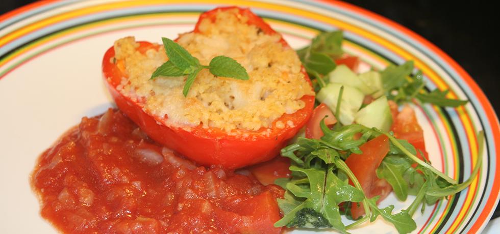 Fylld, röd paprika med smält ost ovanpå, på tallrik med tomatsås och salladsblad