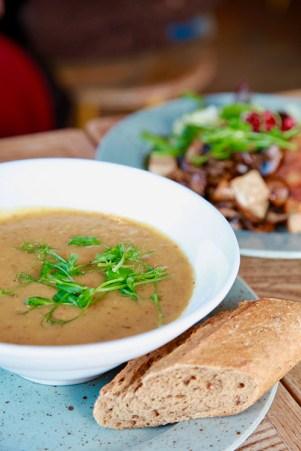 Vit skål med soppa i, toppad med färskt grönt. Ett bröd ligger vid sidan.