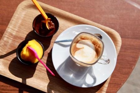 Två små glassbägare på en bricka, till höger en kopp kaffe.