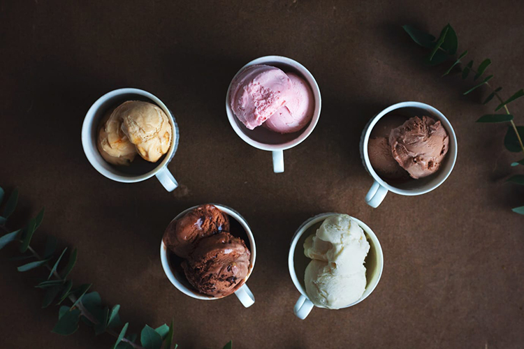 Fem vita koppar med glass i olika färger sedda uppifrån