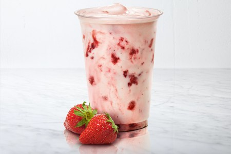 Plastglas med lock med milkshake i med jordåubbsbitar. Två jordgubbar ligger framför