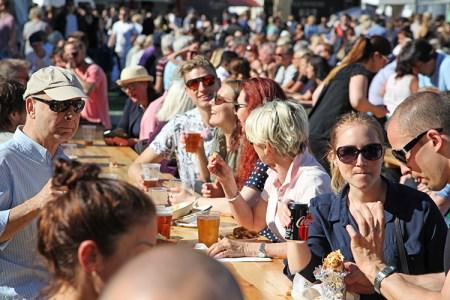 En mängd personer sitter ute vid långbord och äter och dricker
