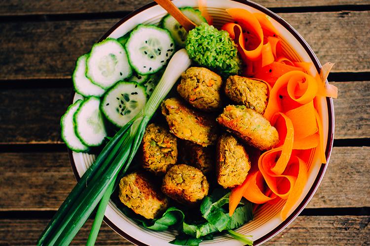 Skål med färsk gurka, salladslök strimlad morot och falafel i mitten