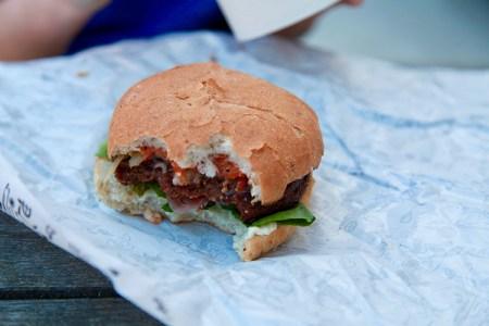 Vegansk hamburgare där det har tagits några tuggor på den, sallad och grönsaker sticker ut under brödet