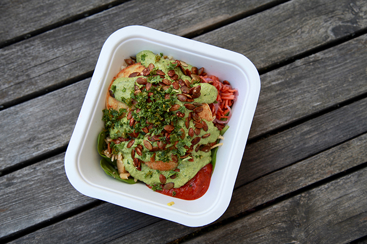 Sallad i fyrkantig vit engångstallrik med quinoa och veganska plättar toppat med grön röra och örter