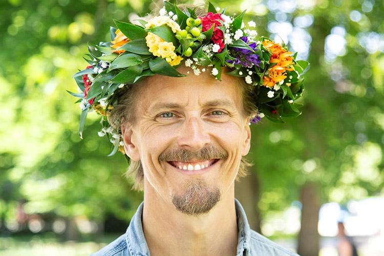 Porträtt på vit man med skägg, han bär en blomsterkrans i håret
