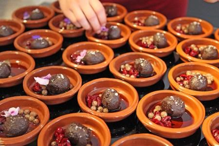 Små skålar med en kula chokladcremoso i garnerat med sås och bär