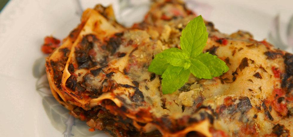 En rektangulär bit lasagne, toppad med mynta på en tallrik