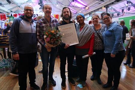 Sex personer bredvid varandra ler med diplom och blommor