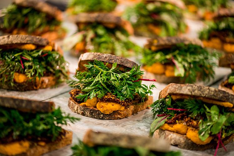 Flera mackor bredvid varandra, fyllda med orange hummus och grönsaker