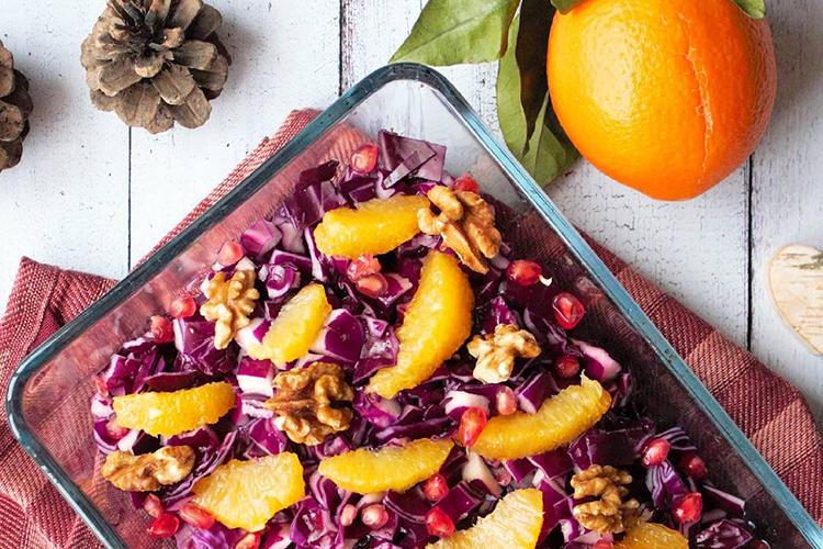 Rödkålssallad med apelsin, valnötter och granatäpple i en glasform. Apelsin och en kotte bredvid
