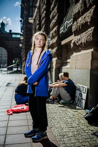 En flicka med långt ljust hår, blå hoodie och svarta byxor utanför en byggnad