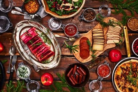 Korvar, frukt och röror på ett träbord med granris och äpplen som dekoration