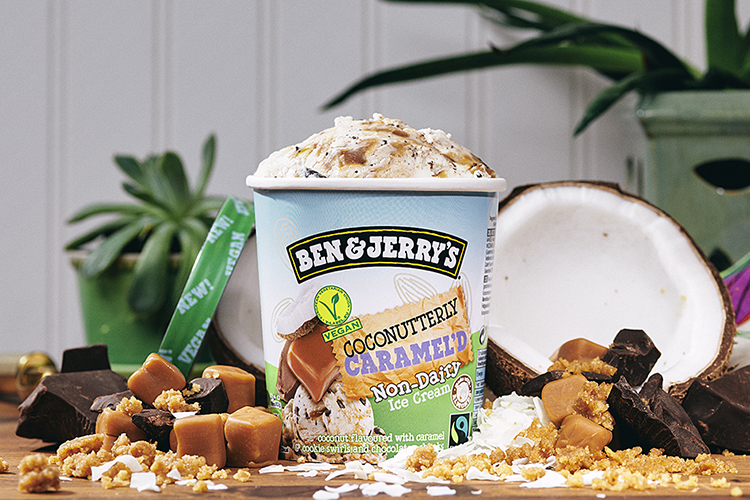 En Ben & Jerrys glassförpackning med en öppnad kokosnöt i bakgrunden. Kola till vänster