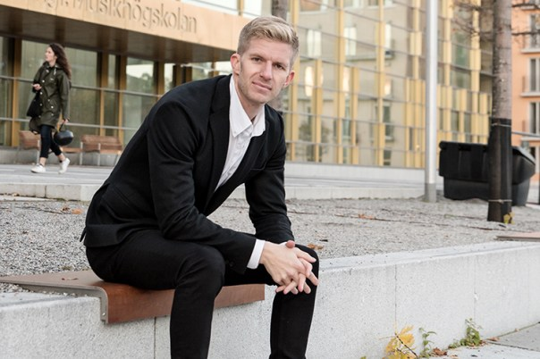 Blond man i svart kostym och vit skjorta sitter på en stenbänk utanför en byggnad