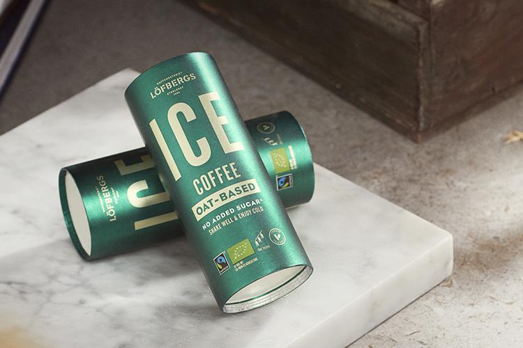 Två gröna, cylinderformade förpackningar med texten ICE coffee i guld