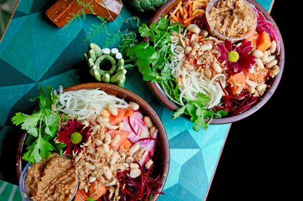 Två skålar i teak med sallad, en blomma och en röra