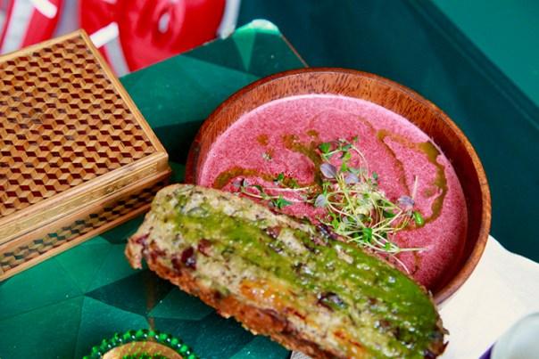 En skål med röd soppa i med ett bröd vid sidan