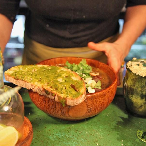 En skål med linsgryta med ett bröd vid sidan