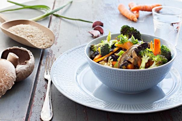 En vit skål med grönsaker, till vänster en brödskiva och en gaffel